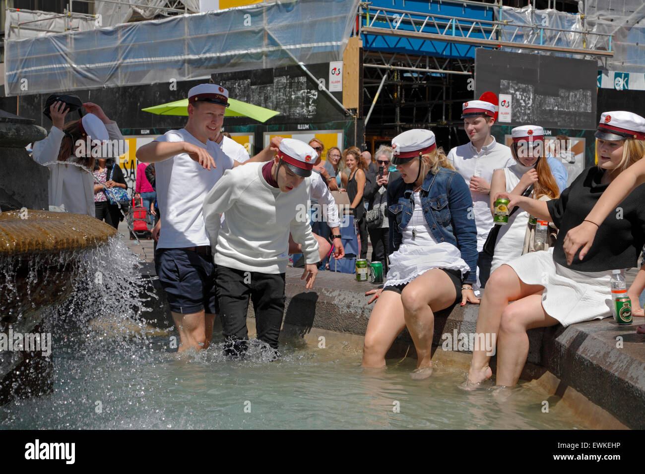 Danish students celebrate their high school graduation by doing the famous dip or plunge into the Stork Fountain - Stock Image