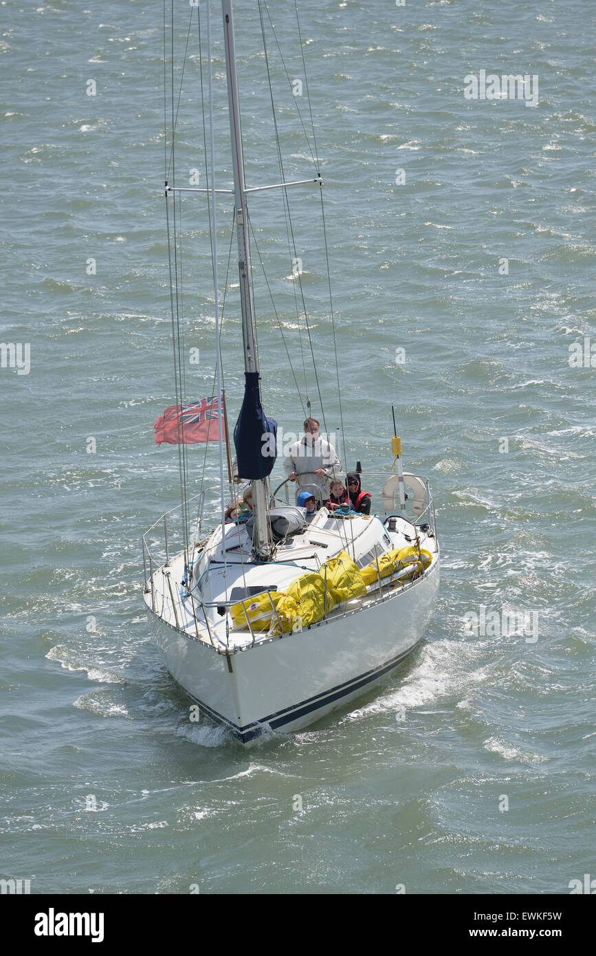 Sailing yacht motoring from harbour to sea in the Solent - Stock Image