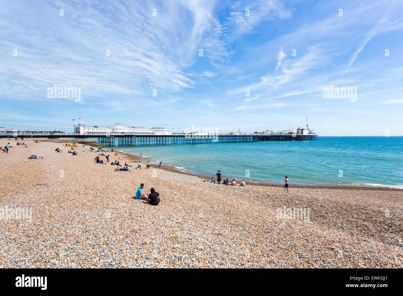 The shingle beach at Brighton, East Sussex, UK in summer and the Palace Pier (Brighton Pier) on a sunny day - Stock Image