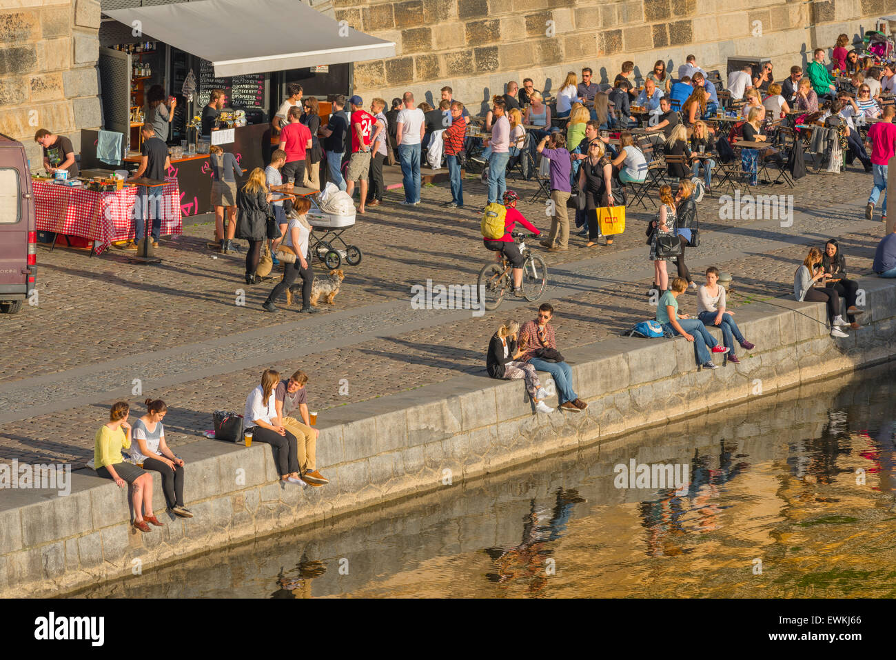 Prague river, view of young people gathered along the embankment of the River Vltava in Prague on a summer afternoon, - Stock Image