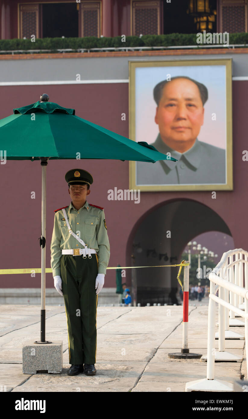 Guard stands at attention before Mao portrait at the Gate of Heavenly Peace, Tienanmen Square, Beijing, China - Stock Image