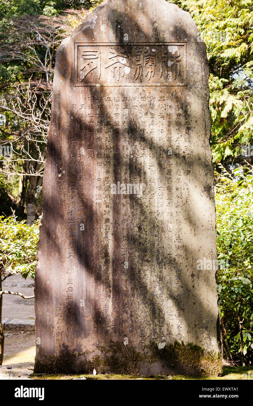 Japan, Kyoto, Arashiyama. Nison-ji Temple. Sacred stone with inscriptions on, in open woodland - Stock Image