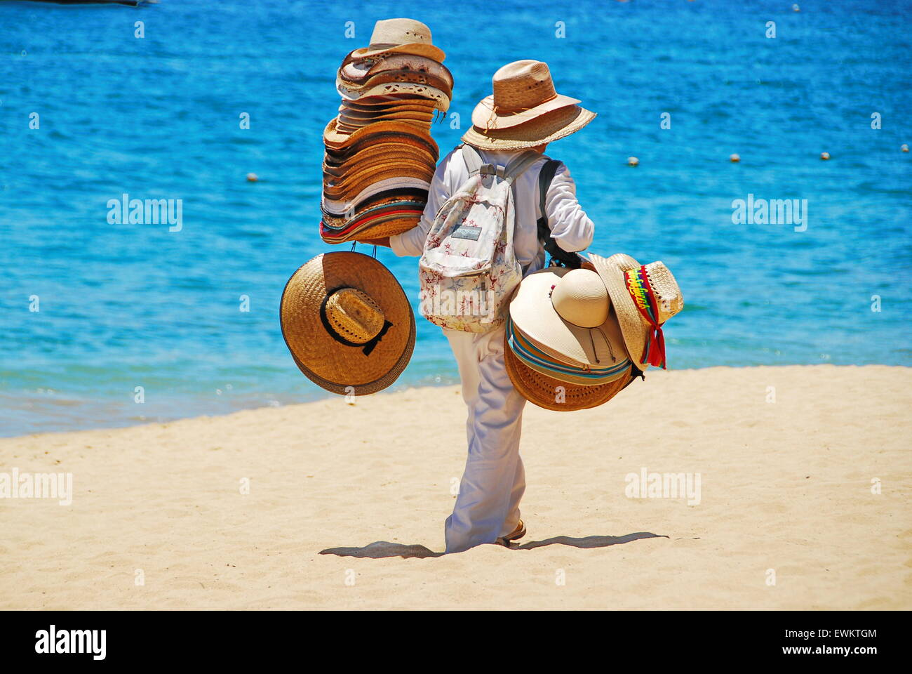 69898e1a5fcc8 Local man selling straw hats on the beach in Cabo San Lucas