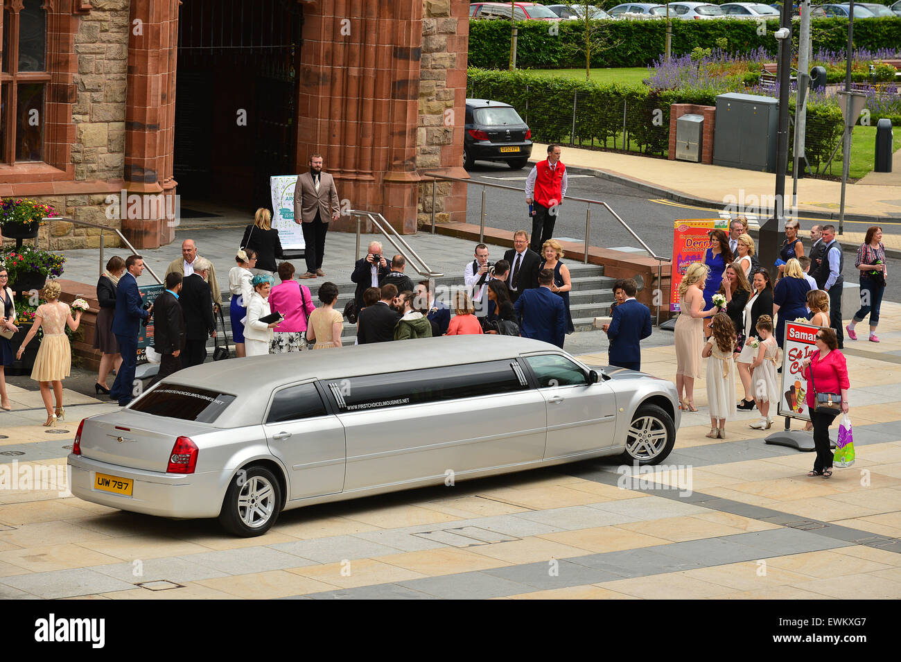 Wedding grout arrives by 8 seater silver Chrysler Stretch Limousine at the Guildhall, Derry, Londonderry, Northern - Stock Image
