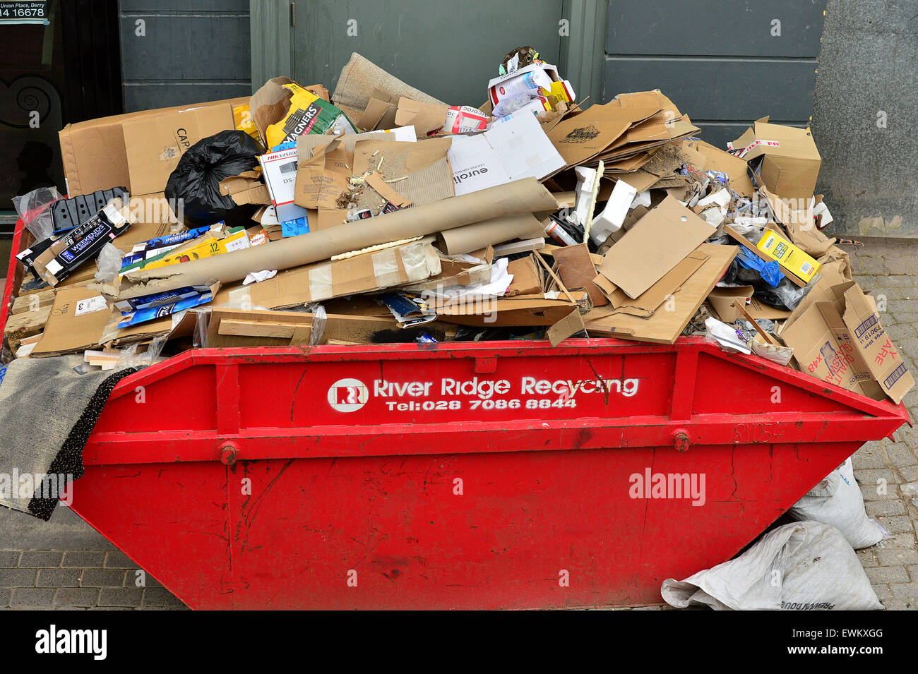 Red recycling skip overflowing with cardboard in Londonderry (Derry), Northern Ireland - Stock Image