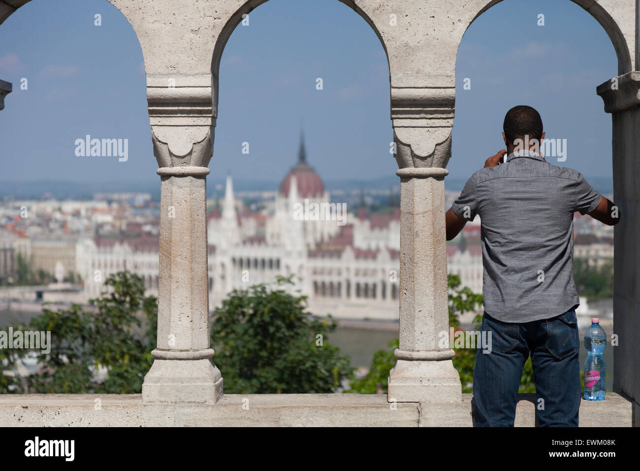 A Tourist photographs the Hungarian Parliament from a vantage point at Fisherman's Bastion in the Castle Hill - Stock Image