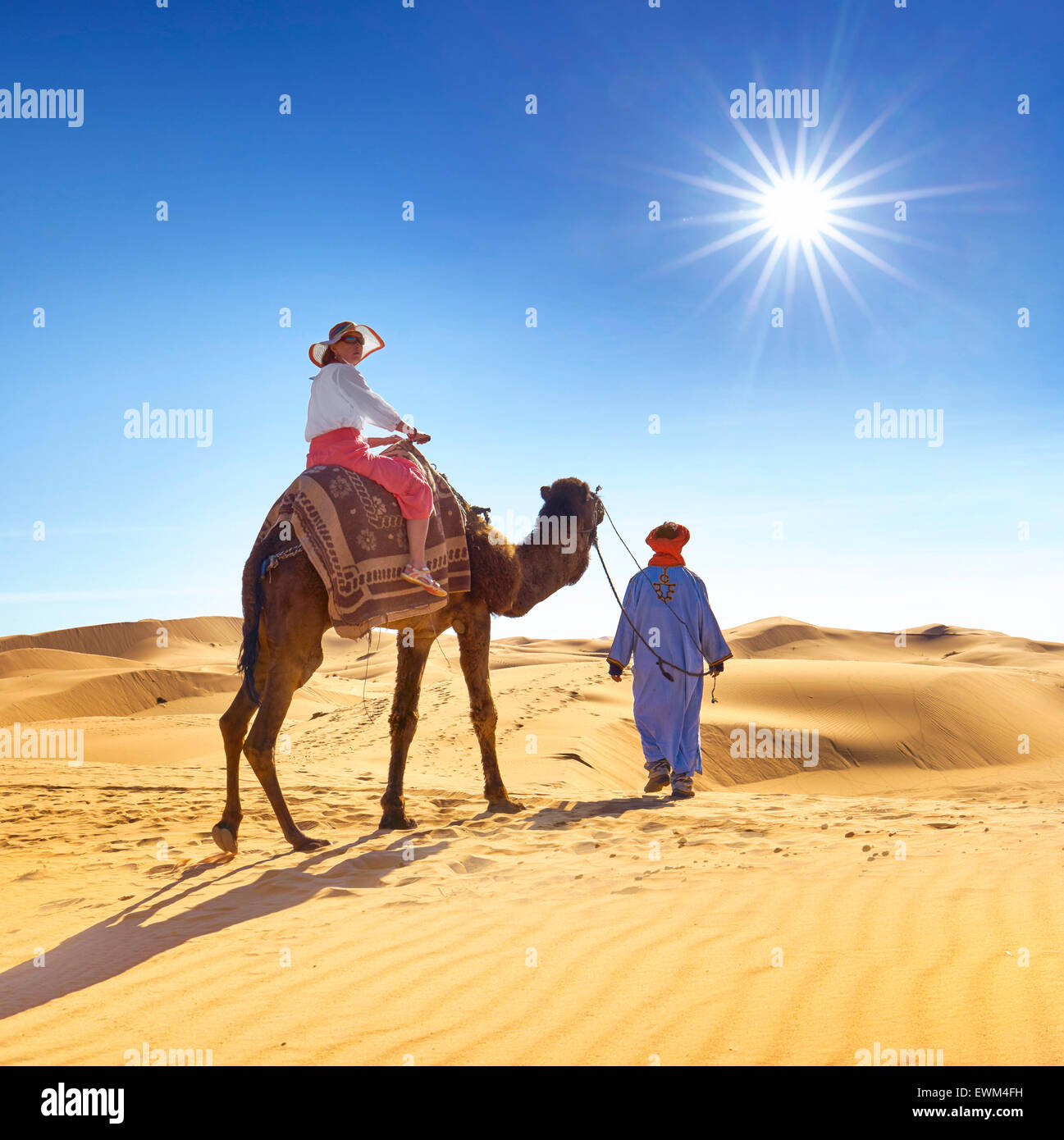 Tourist on camel ride, Erg Chebbi desert near Merzouga, Sahara dunes, Morocco - Stock Image