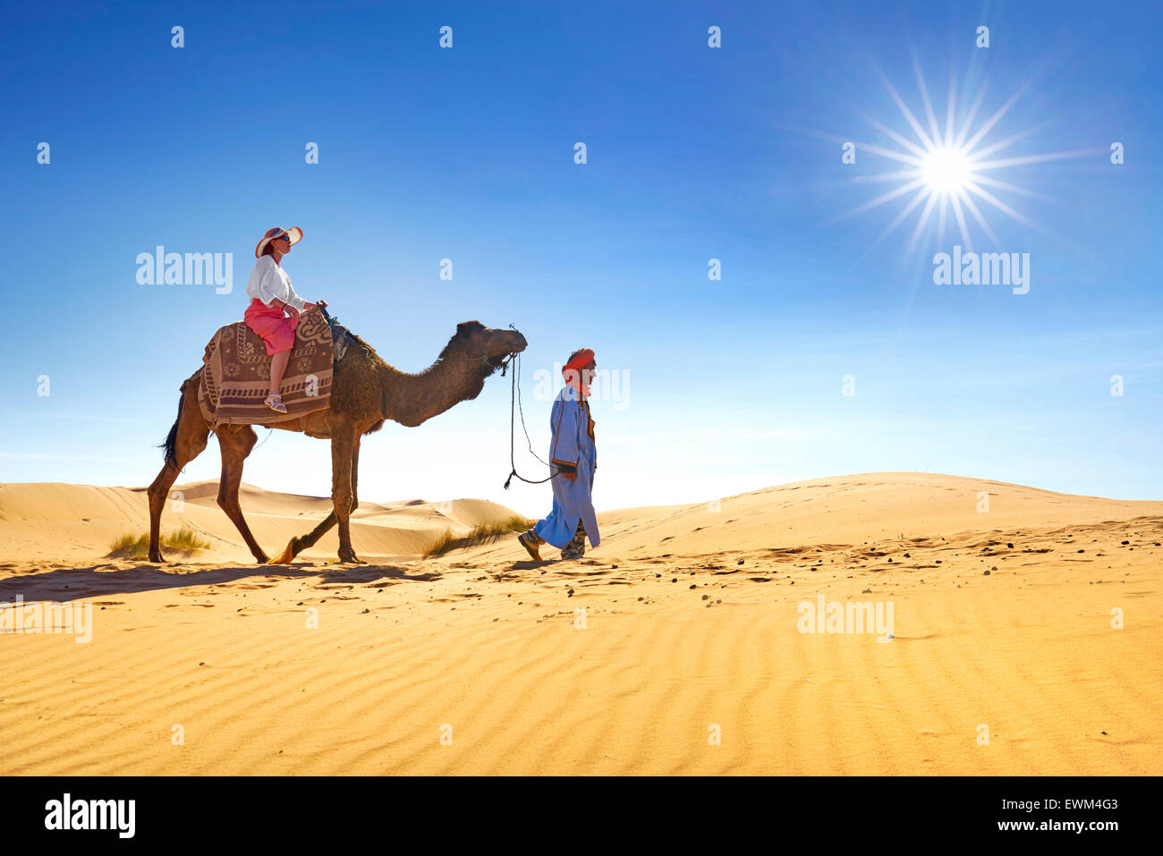 Tourist on camel ride, Erg Chebbi desert near Merzouga, Sahara, Morocco - Stock Image