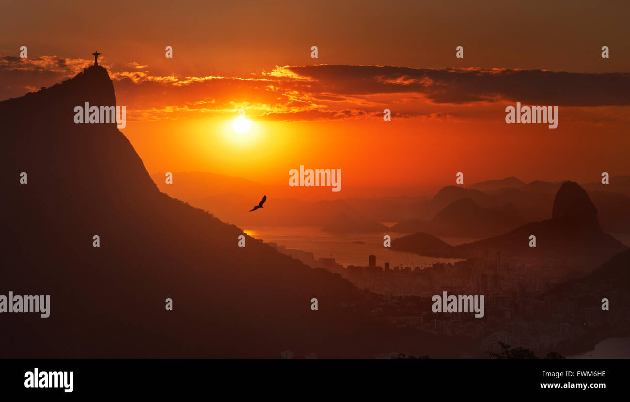 A view of Christ the Redeemer (Cristo Rendentor) atop Mount Corcovado and Sugarloaf (Pao de Acucar) at sunrise in Stock Photo