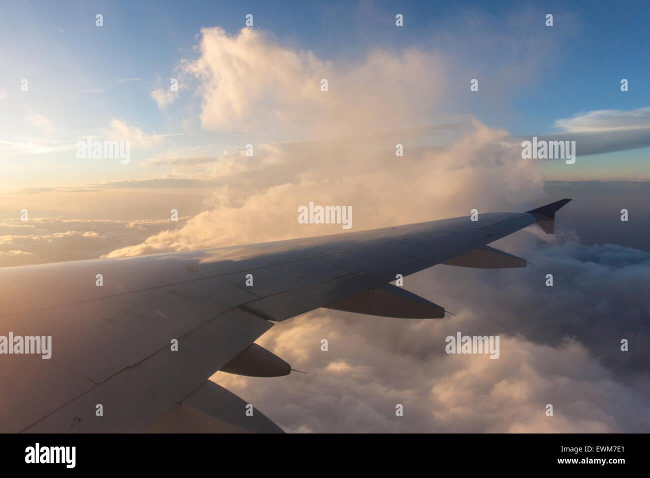 The sun illuminates clouds near an airplane wing. - Stock Image