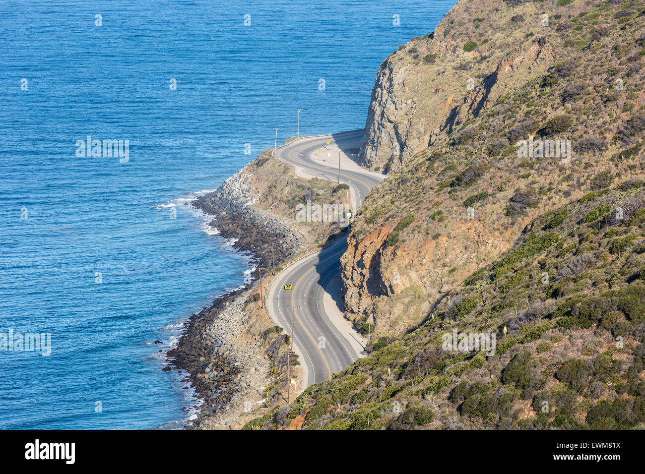 A yellow sports car cruises down Pacific Coast Highway in Malibu, California. Stock Photo