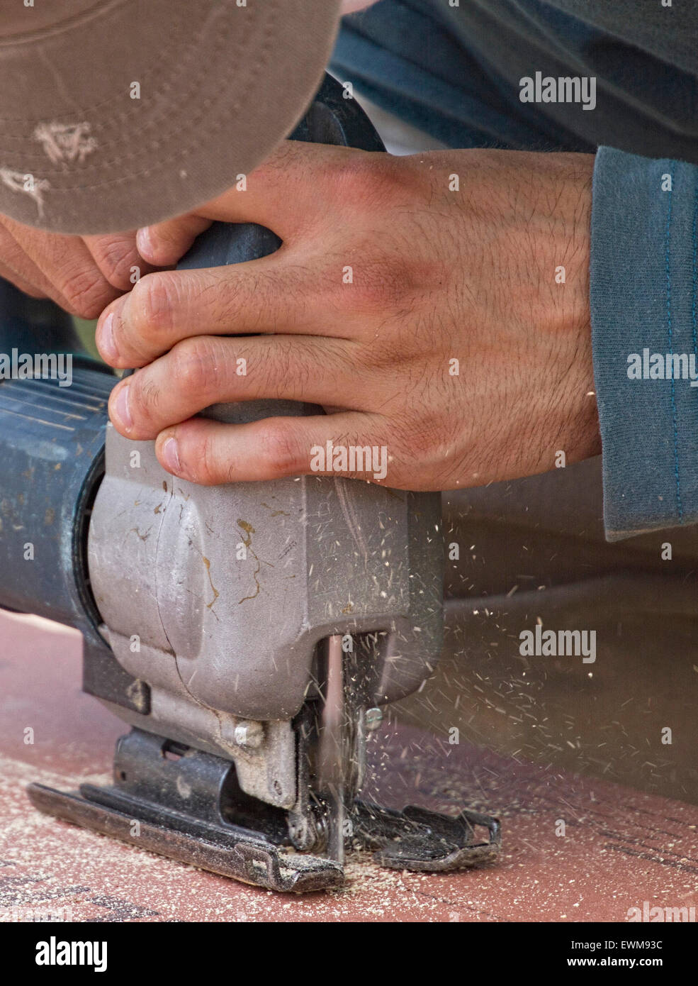Close up of a man's hands operating a table saw tool while cutting plywood - Stock Image