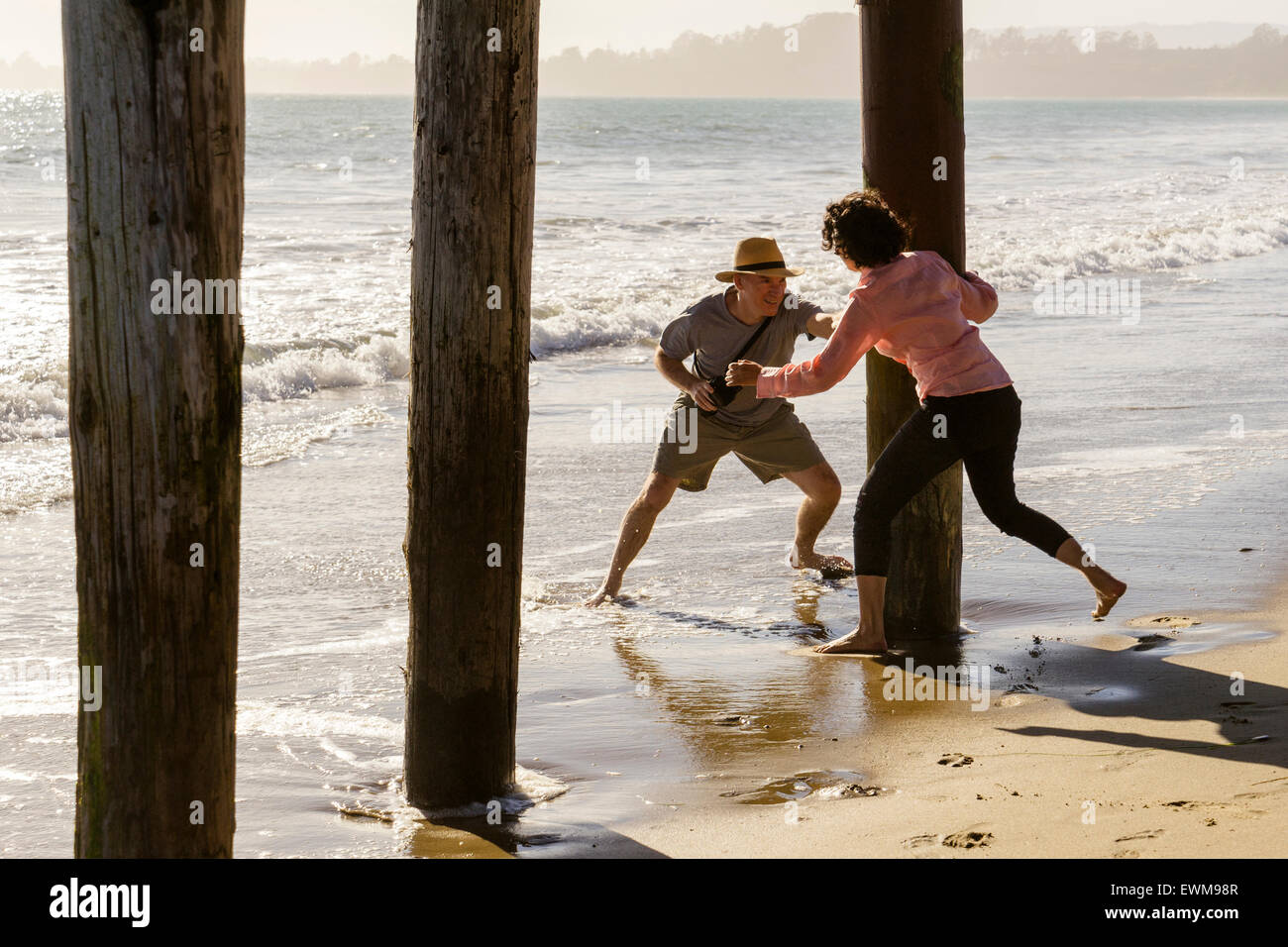 Middle aged man and woman frolicking and chasing each other  around boardwalk piers at the beach - Stock Image