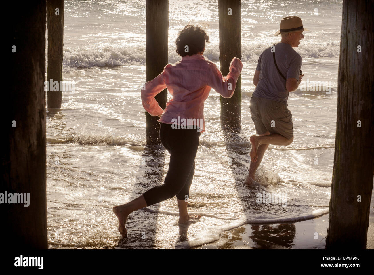Woman chasing a man at the beach, splashing through water under boardwalk piers - Stock Image