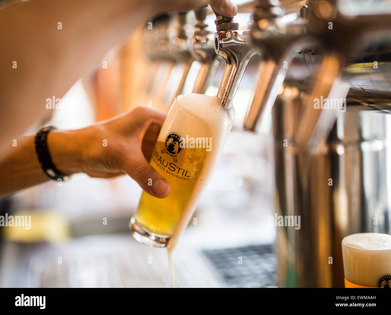 A glass of craft beer is poured in the small brewery 'Braustil, ' located in a former gas station in Frankfurt - Stock Image