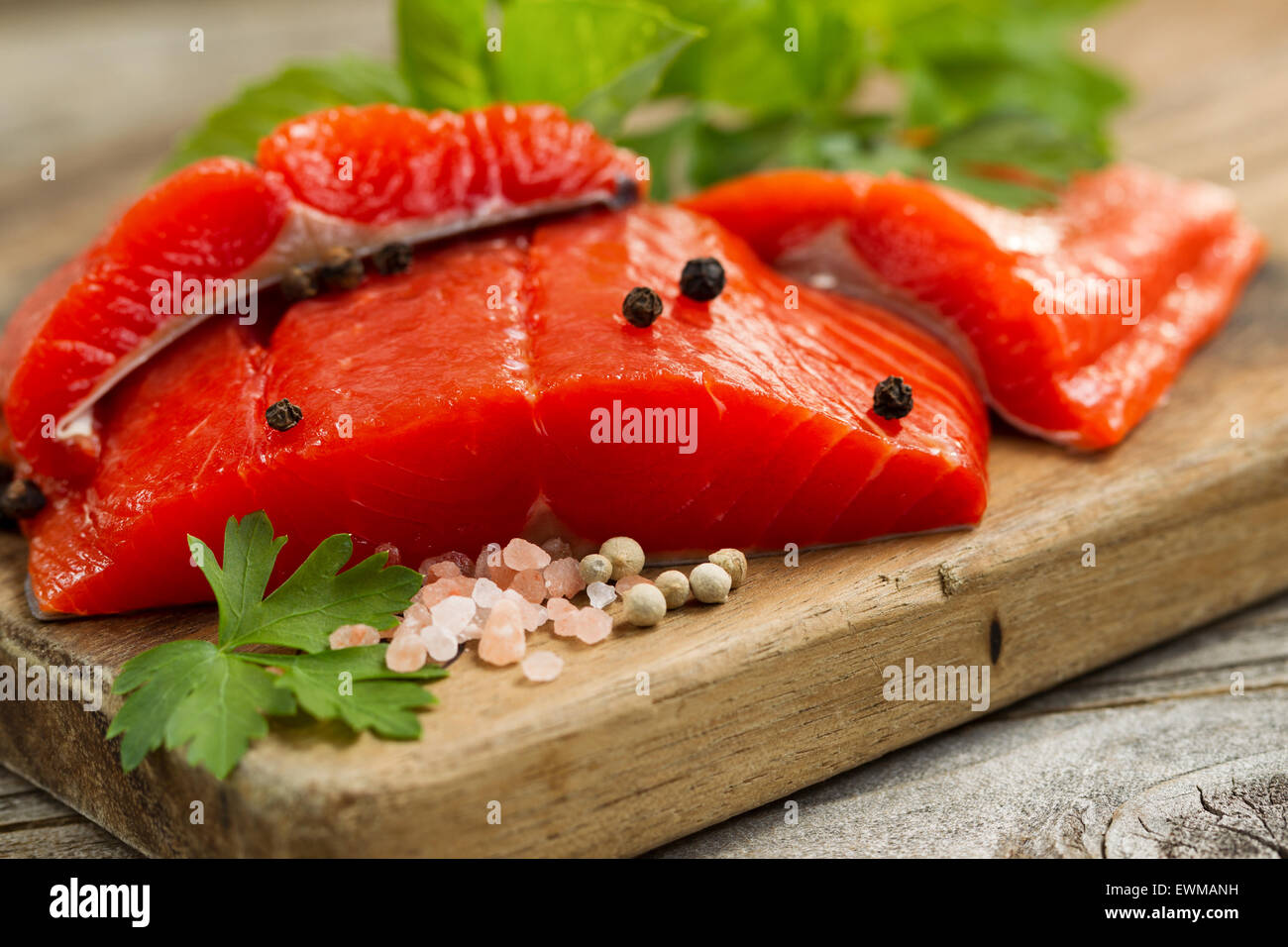 Close up front shot of fresh Copper River red salmon fillets on cutting board, sea salt and herbs. Stock Photo