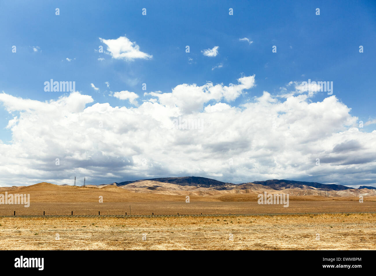 Dramatic photograph of an empty expanse of dry grass with a view of foothills and mountains in the distance - Stock Image