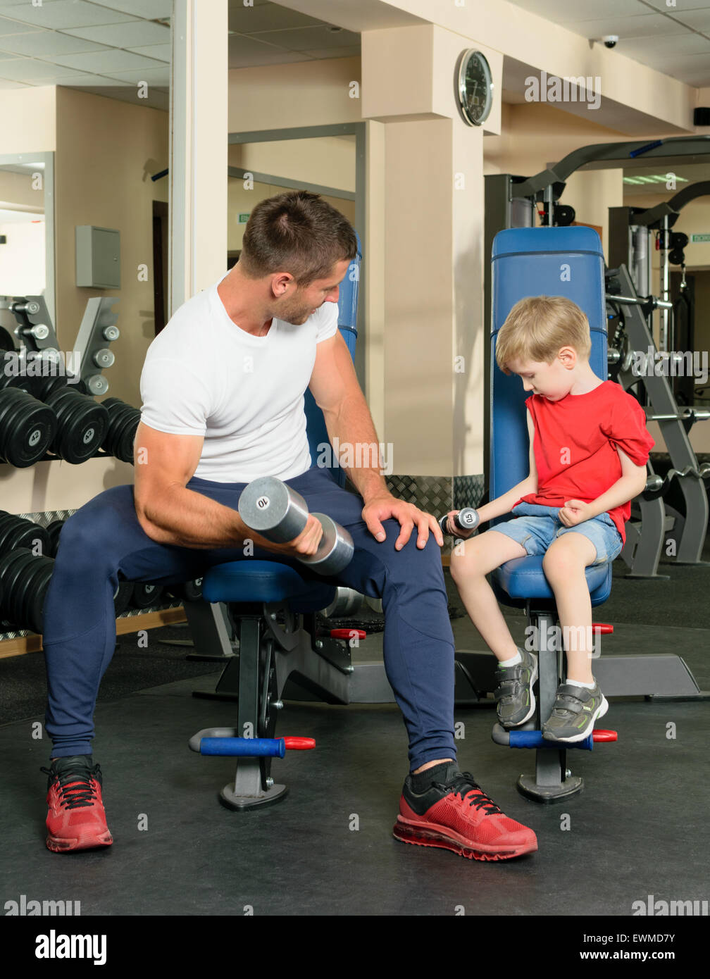 Pope shows little son how to lift weights in the gym - Stock Image