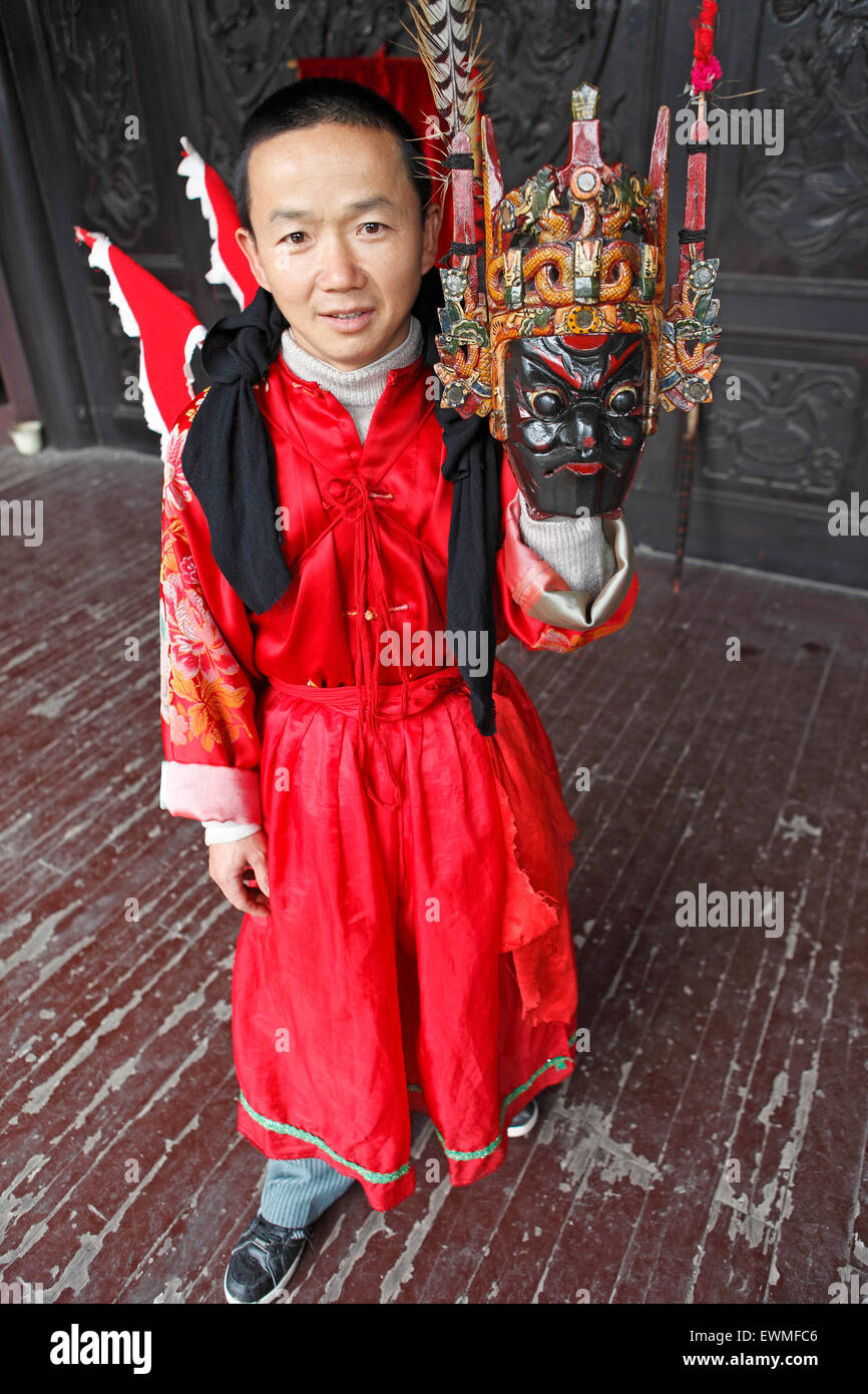 Mask dancer in Ci-Yun Temple holding a traditional mask, Qingyan, Guizhou Province, China - Stock Image