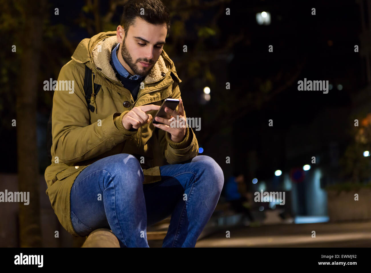 Outdoor portrait of young man using his mobile phone at night. - Stock Image