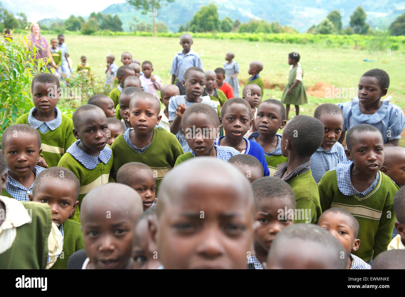 Group of Ugandan school children from a rural school stare at the camera while outside - Stock Image