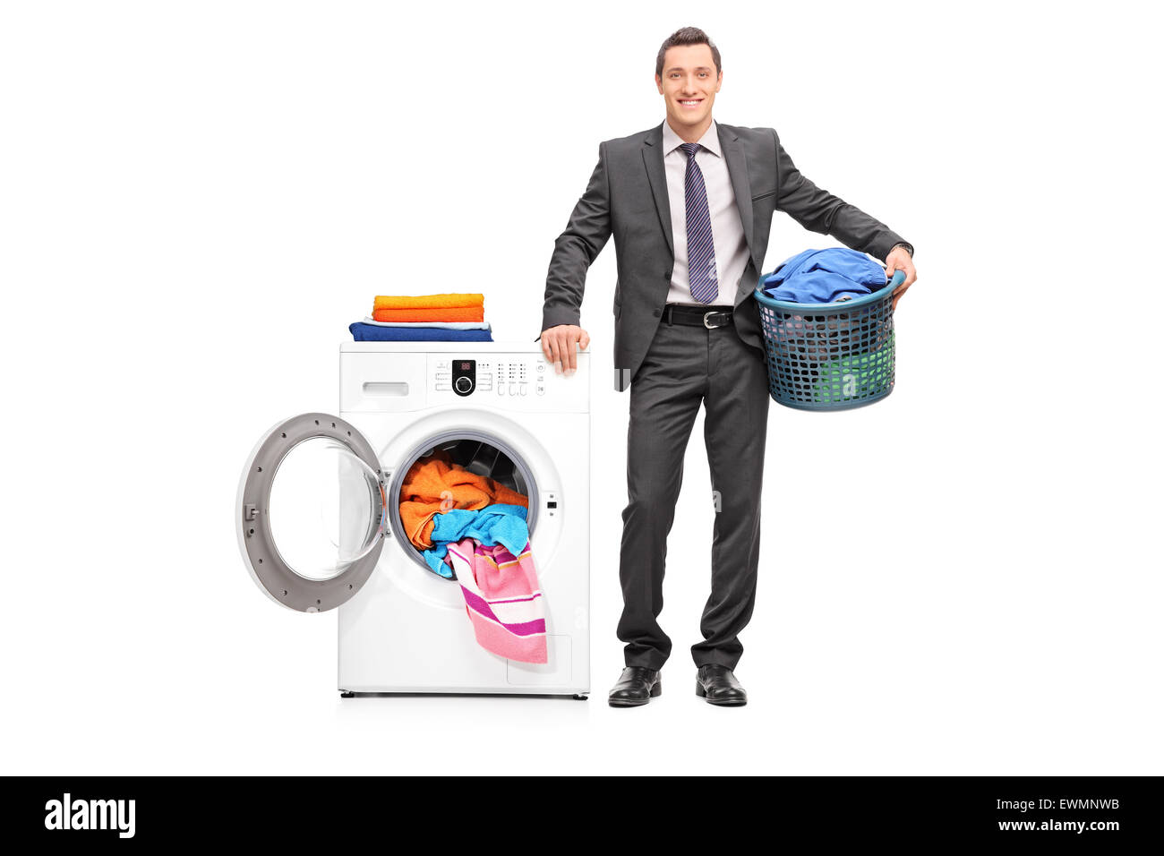Full length portrait of a young businessman holding a laundry basket and posing next to a washing machine isolated - Stock Image