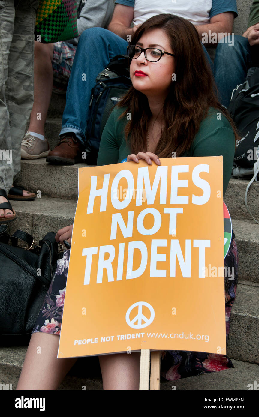 . A woman holds a placard saying 'Homes not trident' - Stock Image