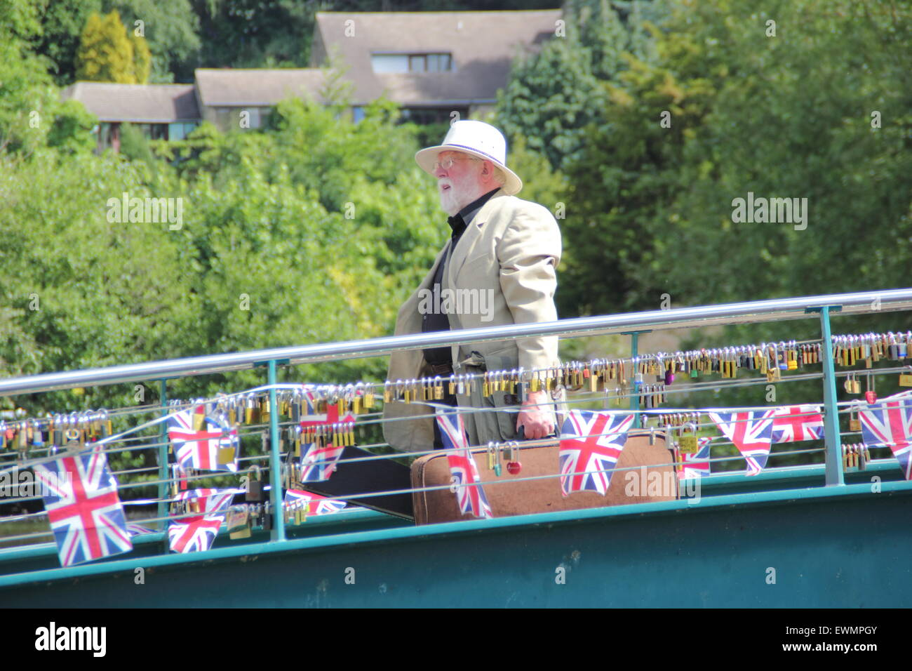 A man wearing traditional British summer attire carries cases across a bunting strewn bridge in Bakewell, England - Stock Image