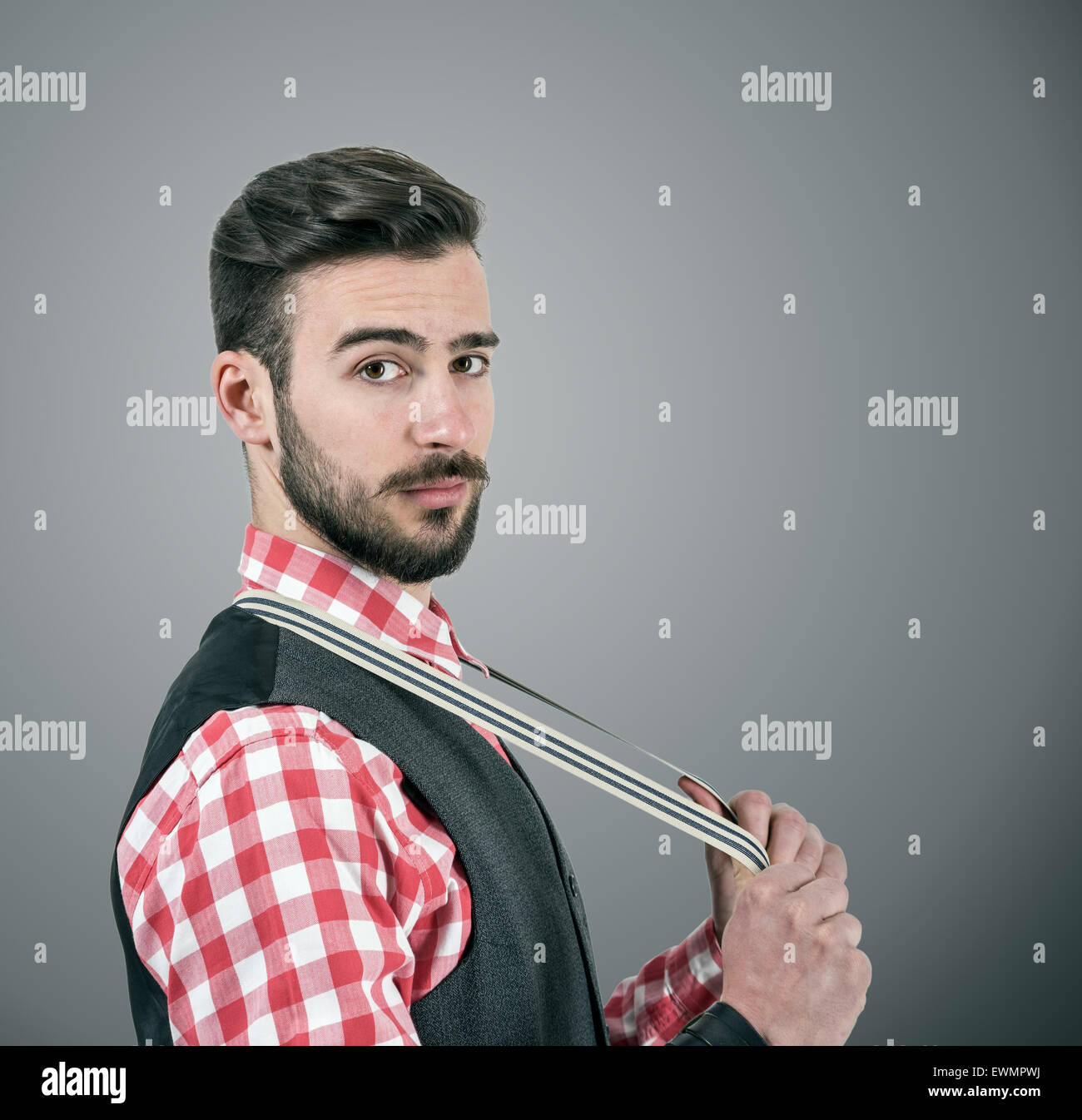 Desaturated portrait of young bearded hipster pulling his suspenders looking at camera over dark grey studio background - Stock Image