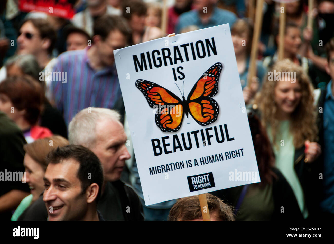 March against austerity, London June 20th 2015. A protester holds a placard saying 'Migration is beautiful'. - Stock Image
