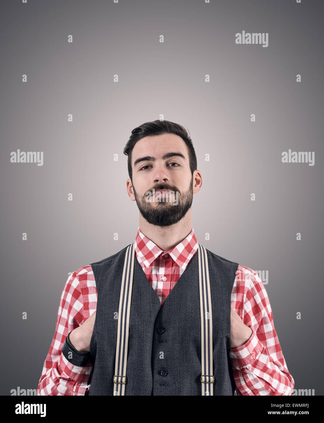 Desaturated portrait of young bearded hipster with hands pushed in his vest over dark gray studio background with - Stock Image