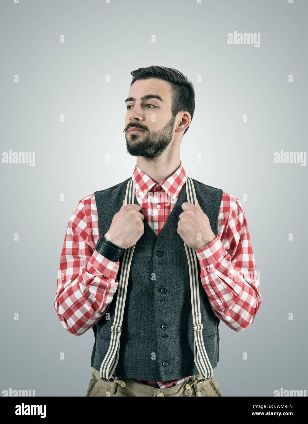 Desaturated portrait of standing young hipster model looking away with raised eyebrow while holding his pants suspenders. - Stock Image