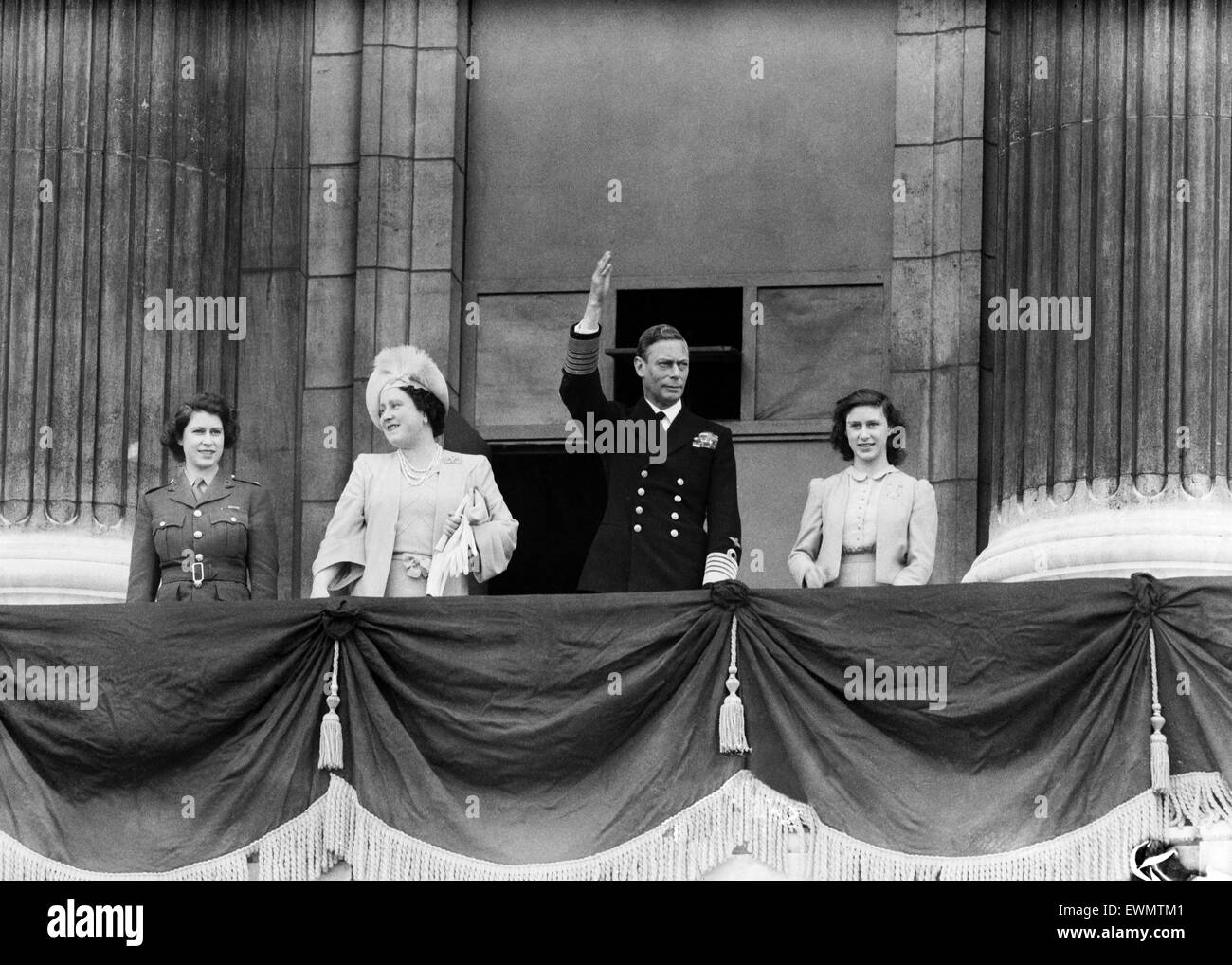VE Day celebrations in London at the end of the Second World War.  King George VI waves to the crowd from  the balcony - Stock Image