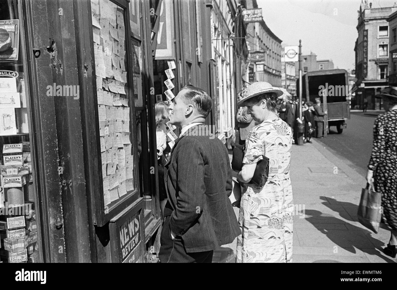 Shoppers looking for a bargain read the small ads outside a Earls Court News Agents. Earls Court. London. SW7. July - Stock Image