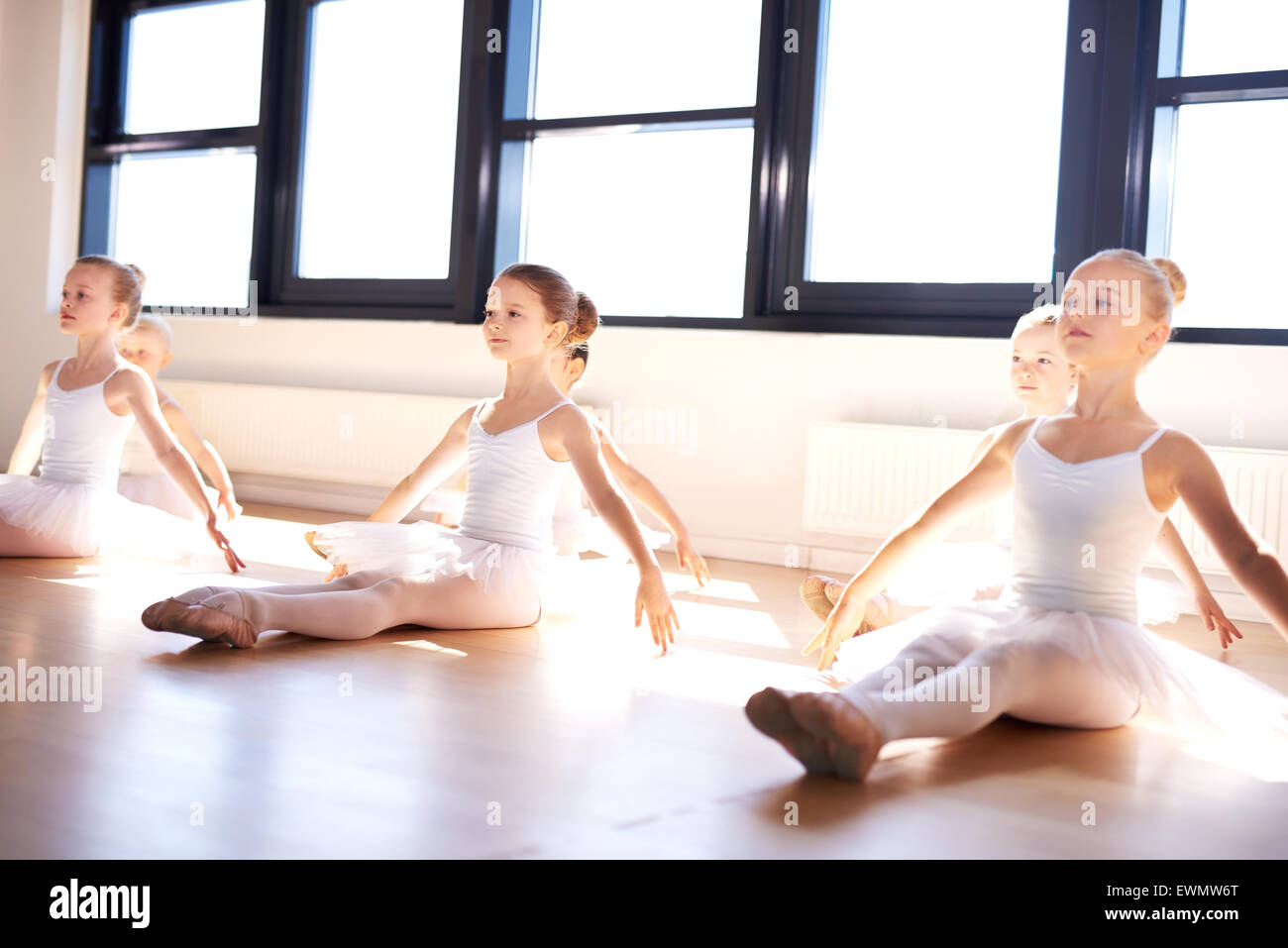 Group of cute graceful little ballerinas in class sitting on the wooden floor of the studio practising a pose with - Stock Image