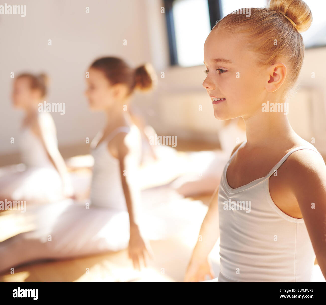 Close up side view of the face of a cute pretty little blond ballerina smiling in class as she practices her poses - Stock Image