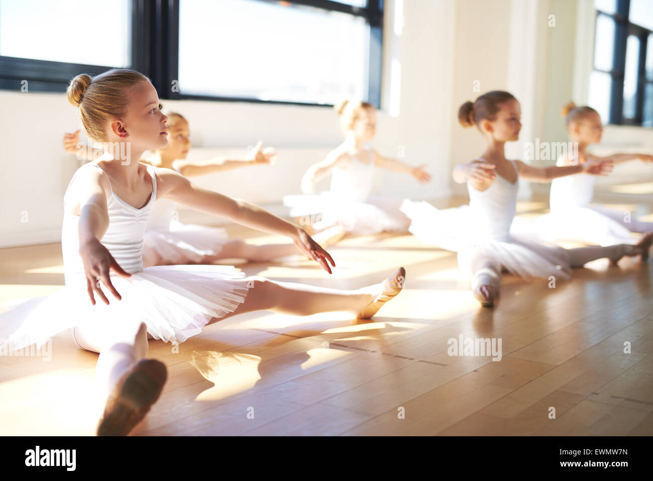 Pretty Young Girls, Wearing White Tutus, Sitting on the Floor at the Studio While Having a Training for Ballet Dance. - Stock Image