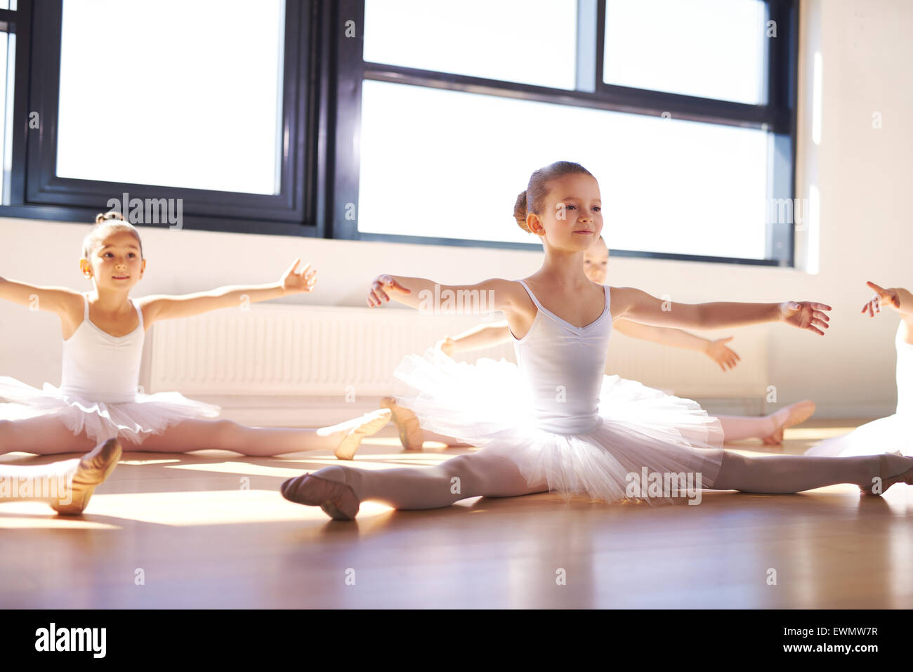 Pretty Young Ballerinas in White Tutus, Sitting on the Floor and Stretching Arms and Legs as Warm Exercise. - Stock Image