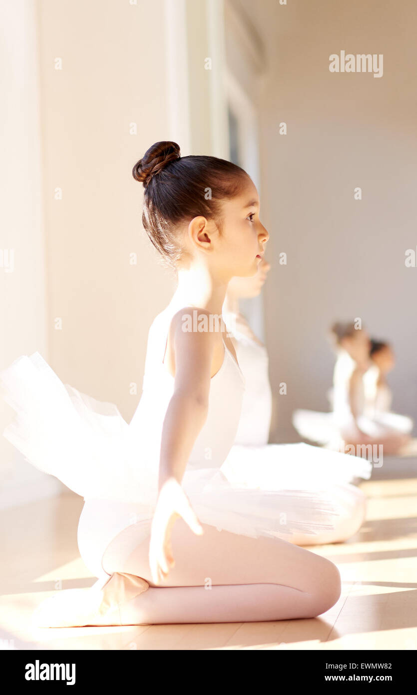 Side View of an Attentive Young Pretty Ballerina Girl During the Ballet Training, Sitting on her Ankle with Arms - Stock Image