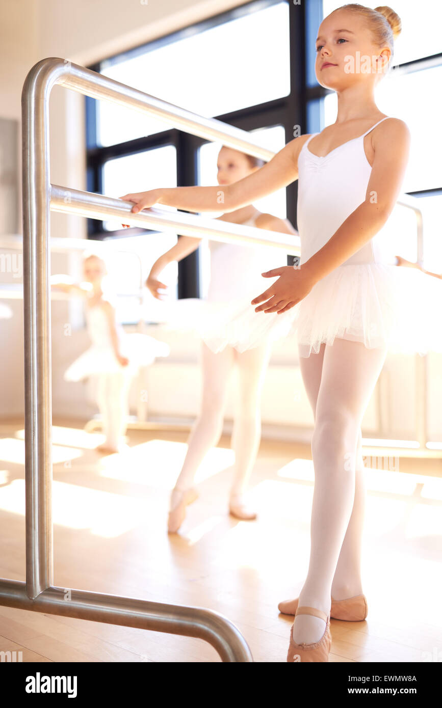 Graceful young girl practicing her ballet in a classical dance studio standing posing at the bar in her white tutu - Stock Image