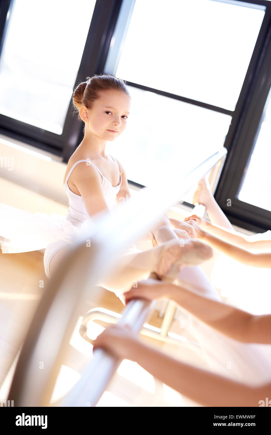 Pretty Smiling Ballet Girl in a Training Exercise at the Studio, Stretching her Leg Using Steel Bar While Looking - Stock Image