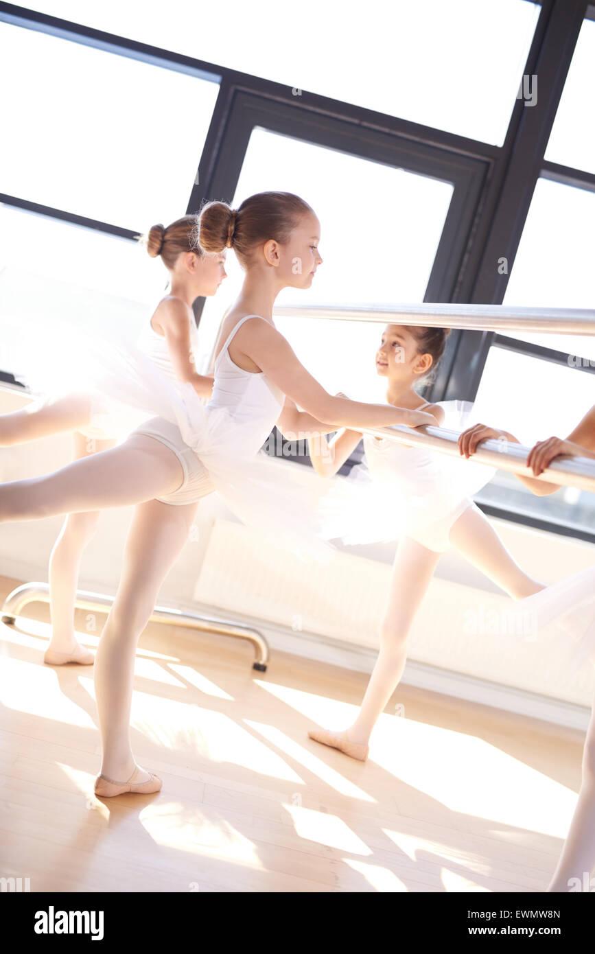 Cute Little Ballet Girls in White Tutu Doing a Reverse Leg Lift While Holding a Horizontal Bar Inside the Studio. - Stock Image