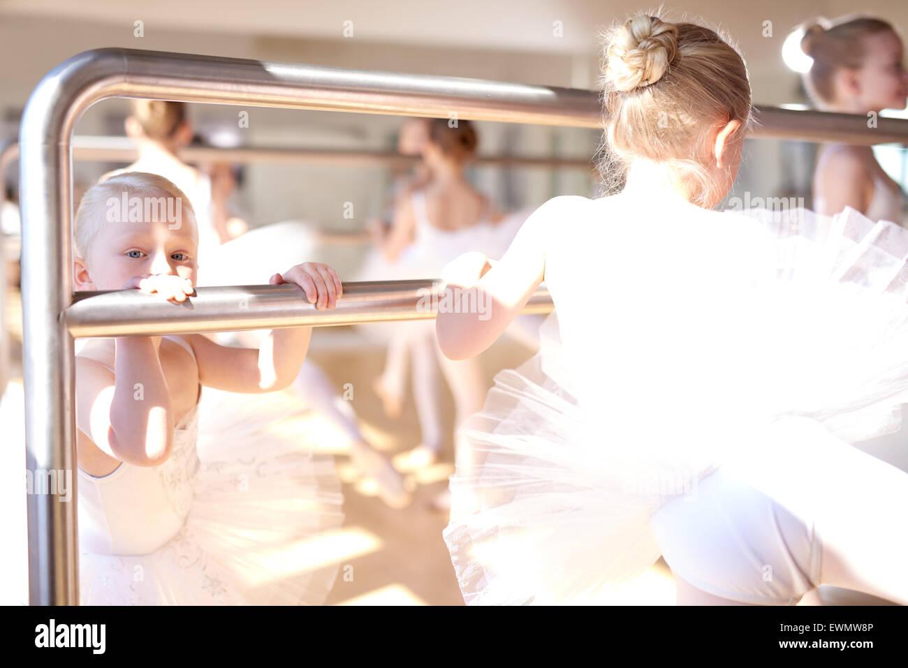 Little White Ballerinas Doing a Stretching Exercise Using a Ballet Horizontal Bar at the Dance Studio. - Stock Image