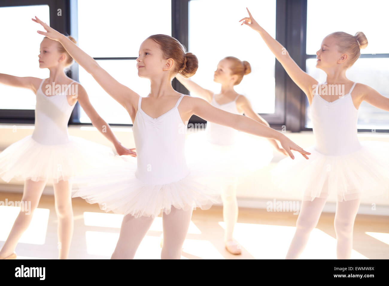 Choreographed dance by a group of graceful pretty young ballerinas practicing during class at a classical ballet - Stock Image