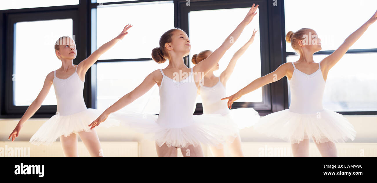Young ballerinas practicing a choreographed dance all raining their arms in graceful unison during practice at a - Stock Image