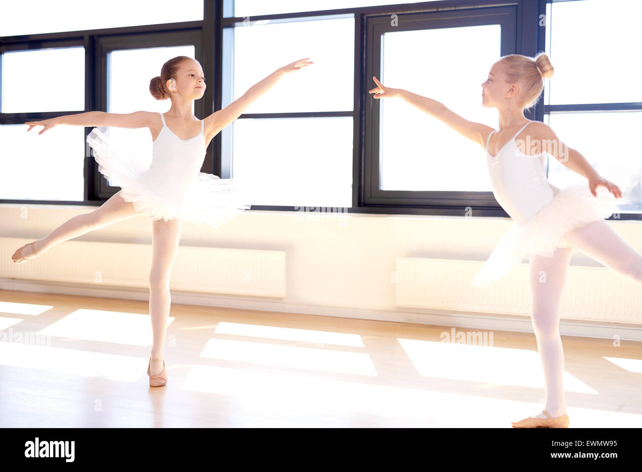 Two graceful little girls practicing a choreographed ballet in a classical ballet studio as they fulfil their dreams - Stock Image