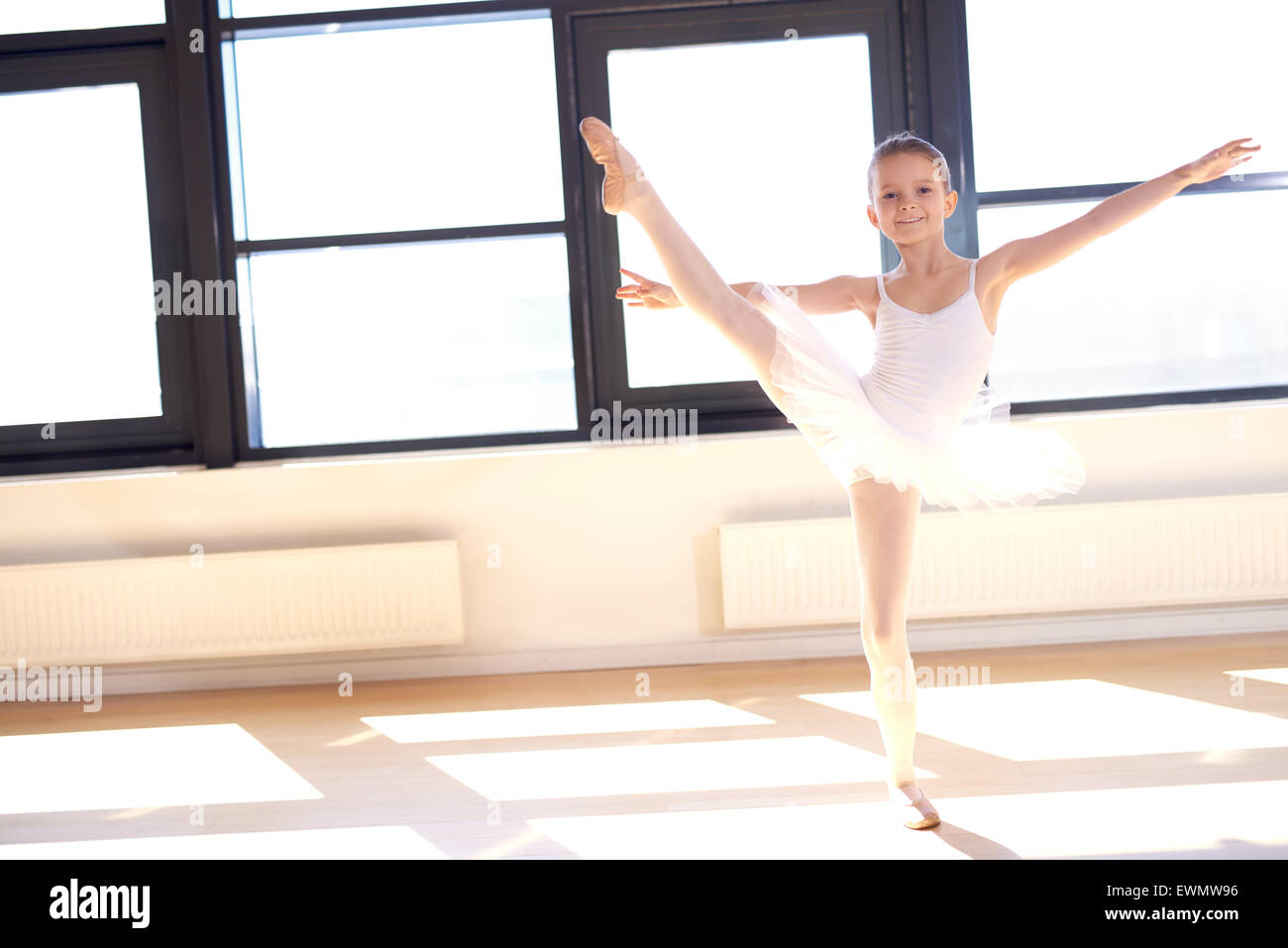 Agile pretty young ballerina practicing her positions in a graceful pose in front of bright windows at a ballet - Stock Image