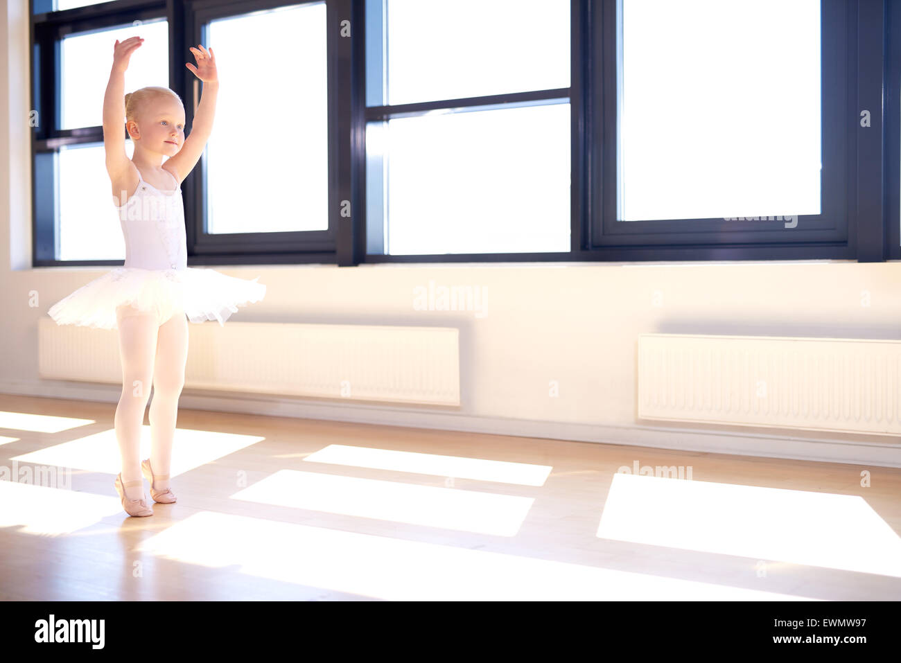Little girl training to be a ballerina standing in a graceful arms raised position in her white tutu and pink satin - Stock Image