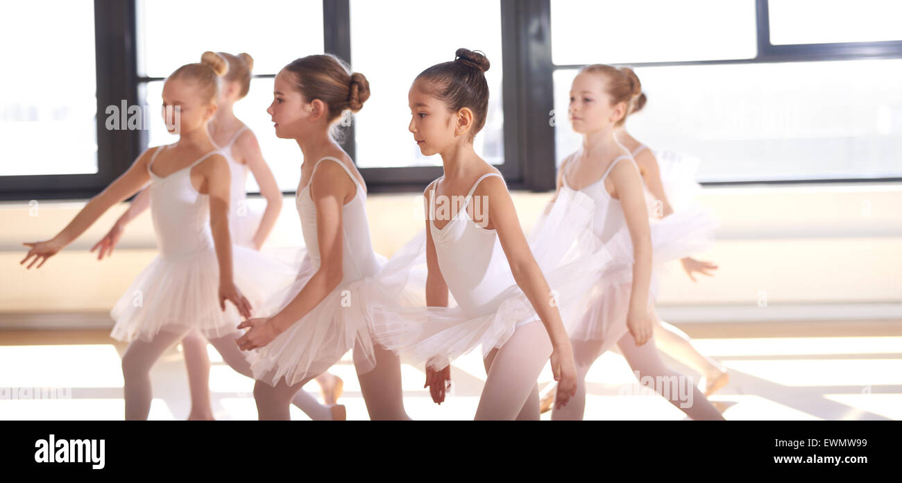 Group of young ballerinas performing a choreographed ballet as they train together at a ballet studio - Stock Image
