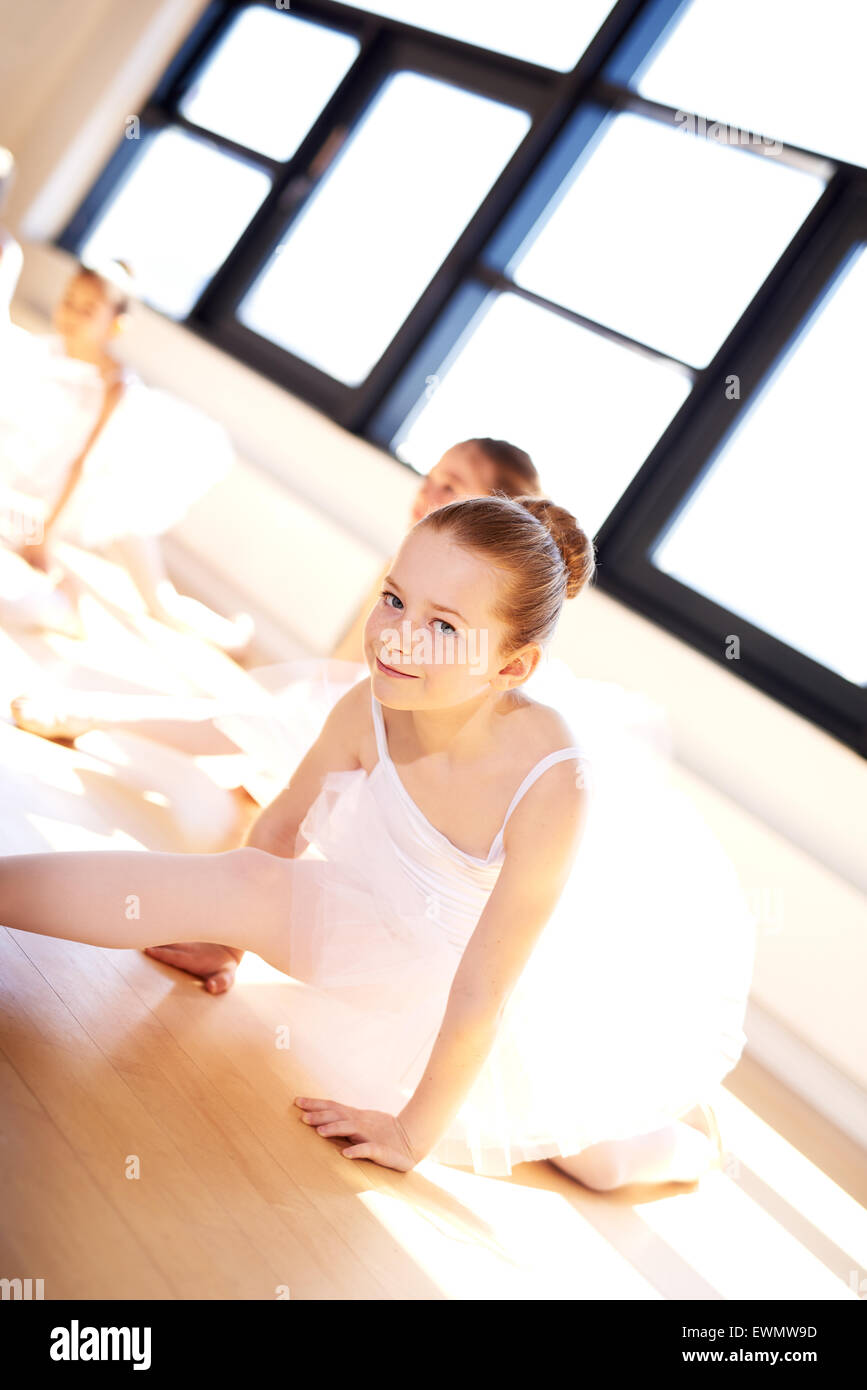 Cute Little Ballerina in White Tutu, Splitting her Legs on the Floor While Looking at the Camera During the Training - Stock Image